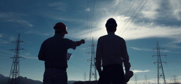 Zwei Ingenieure stehen vor einem Feld mit Hochspannungsleitungen